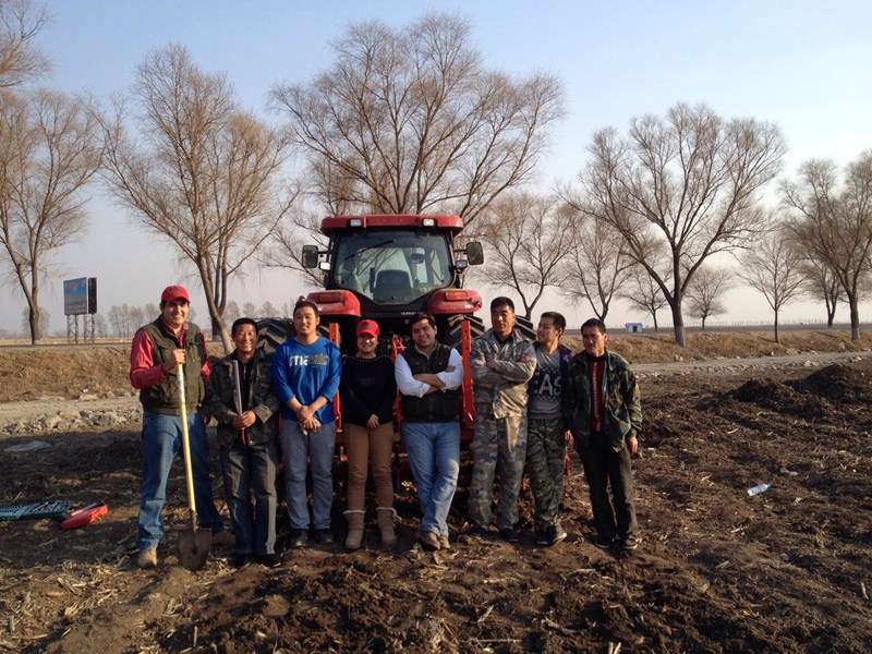 Hong Cui ('Jenny') and farm team with tractor in China
