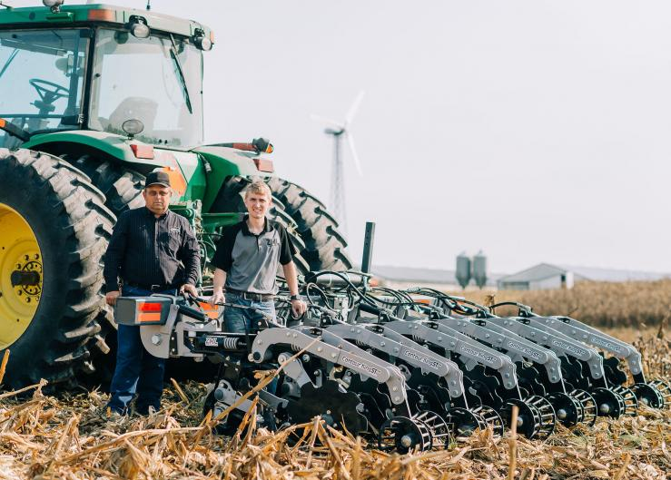 Raymond (left) and Raymond Claire (right) of Zimmerman Manufacturing stand with their strip-till machine.